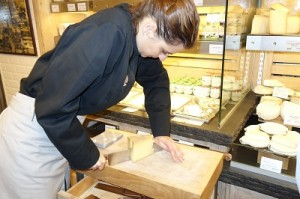 Cutting us a sample of aged cheese