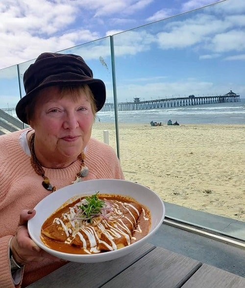 Holding plate of shrimp enchiladas by the beach